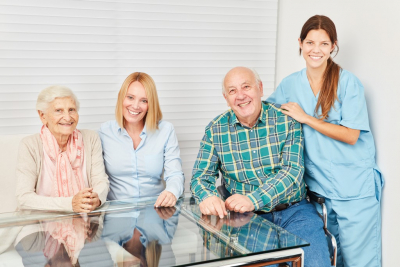 senior couple and their caregivers smiling