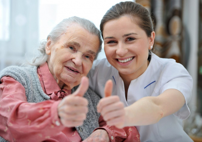 caregiver and senior woman doing thumbs up